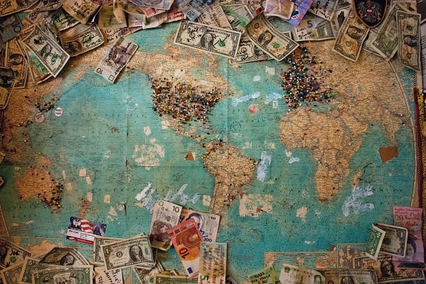 Various global currencies spread across a world map.