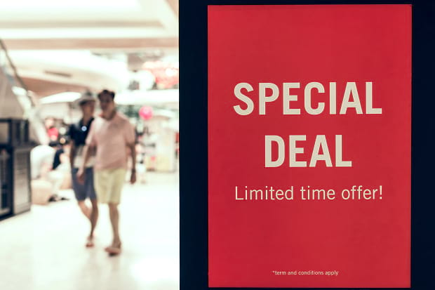 A special deal slide displaying beside a blurred image of people shopping in a mall