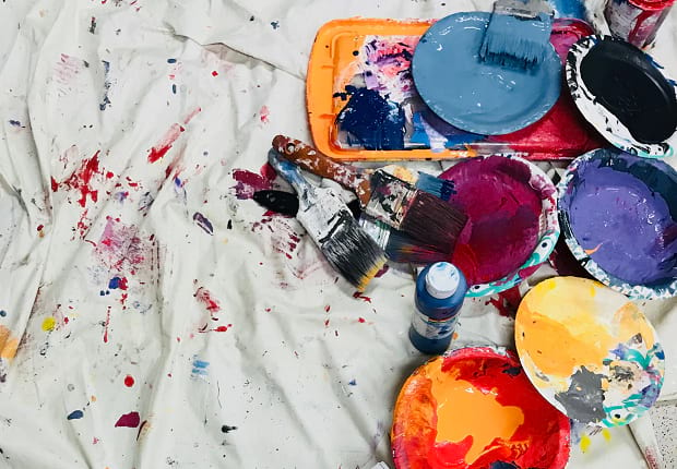 Several brushes and different colors of paint laid out on a white, paint-splattered cloth